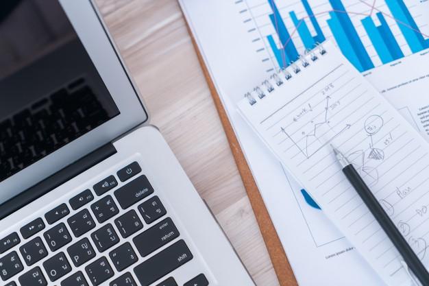 financial charts on the table with laptop 1232 2738 1 - گزارشگری میاندوره ای